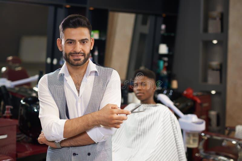 Retrato do barbeiro à moda que olha a câmera na barbearia foto de stock