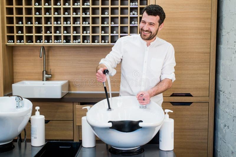 Retrato do barbeiro feliz com a torneira de água perto do dissipador no barbeiro do salão de beleza fotografia de stock