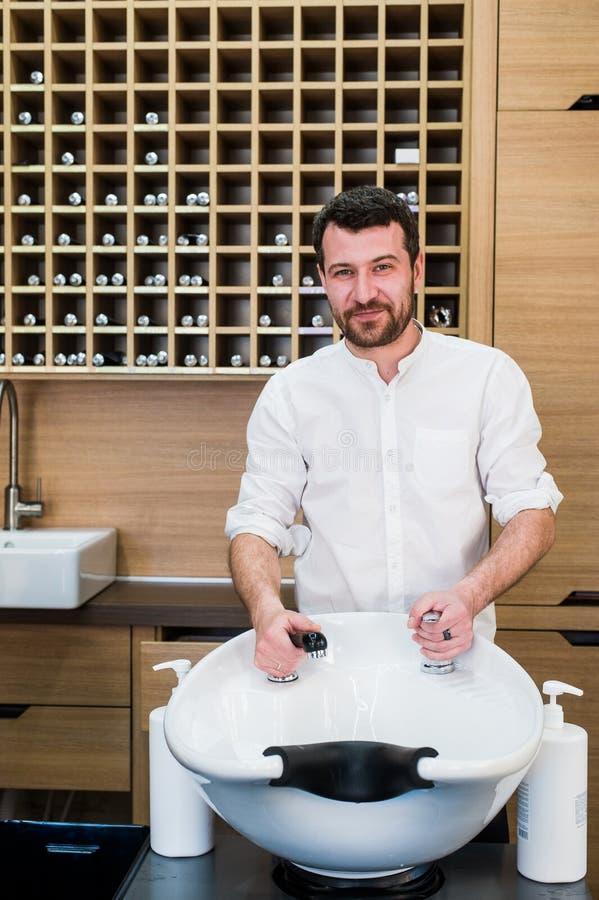 Retrato do barbeiro feliz com a torneira de água perto do dissipador no barbeiro do salão de beleza foto de stock