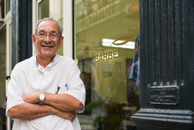 Retrato do barbeiro idoso que sorri no salão de beleza de cabelo fotografia de stock