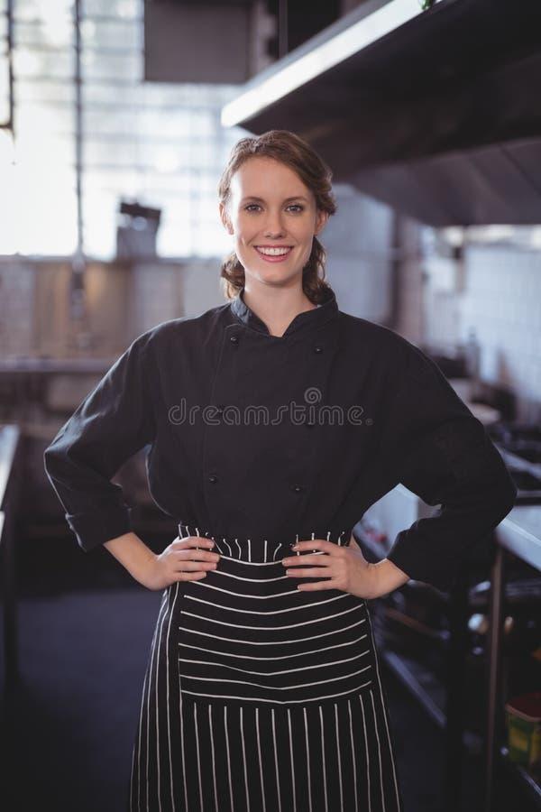 Retrato do barista fêmea novo de sorriso que está com mãos no quadril na cozinha fotos de stock