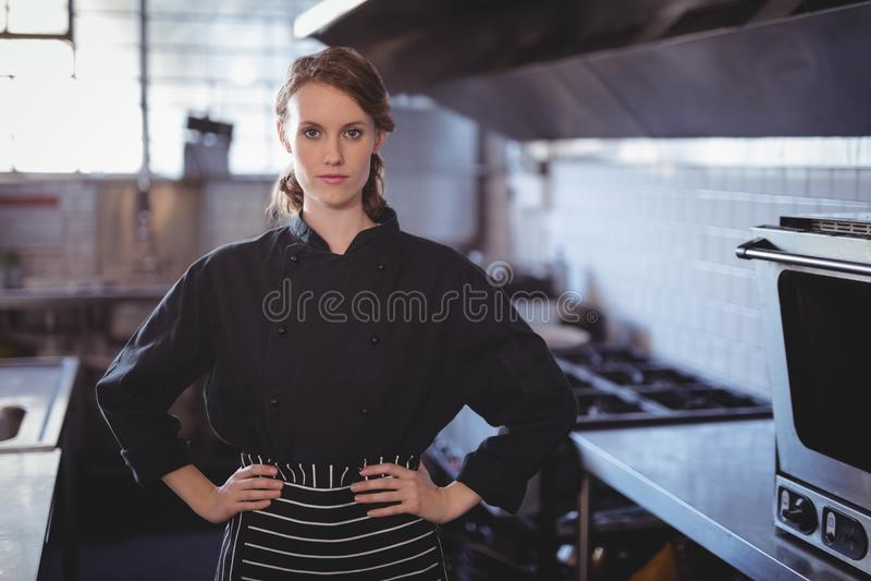 Retrato do barista fêmea novo que está com mãos no quadril na cozinha foto de stock