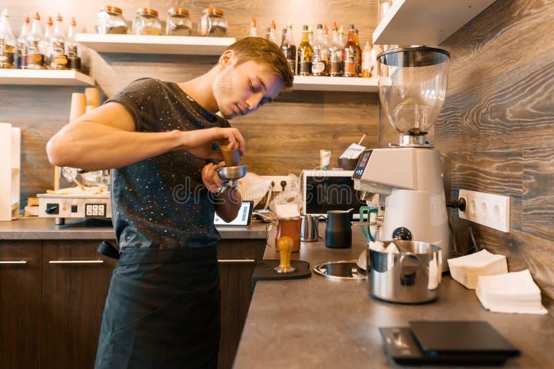 Retrato do barista masculino novo que faz bebidas Conceito do negócio da cafetaria foto de stock