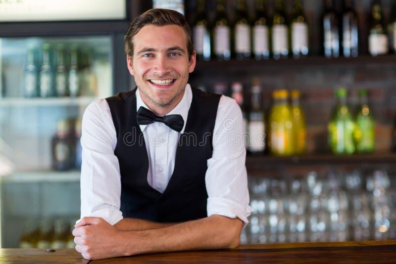 Retrato do barman que inclina-se no contador da barra fotos de stock