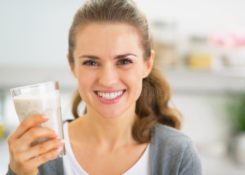Retrato do batido bebendo da jovem mulher feliz na cozinha imagens de stock