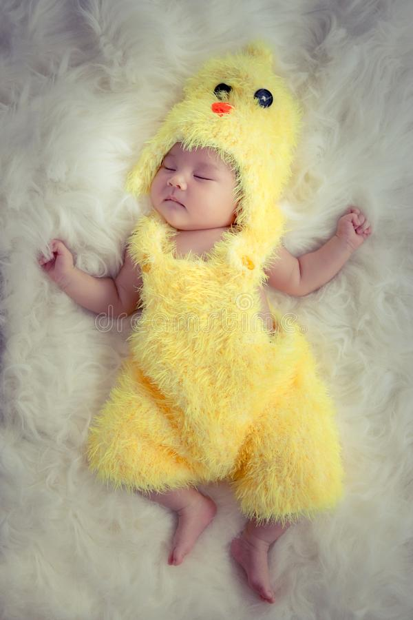 Retrato do bebê: Bebê asiático de sono feliz que veste o galo amarelo imagens de stock