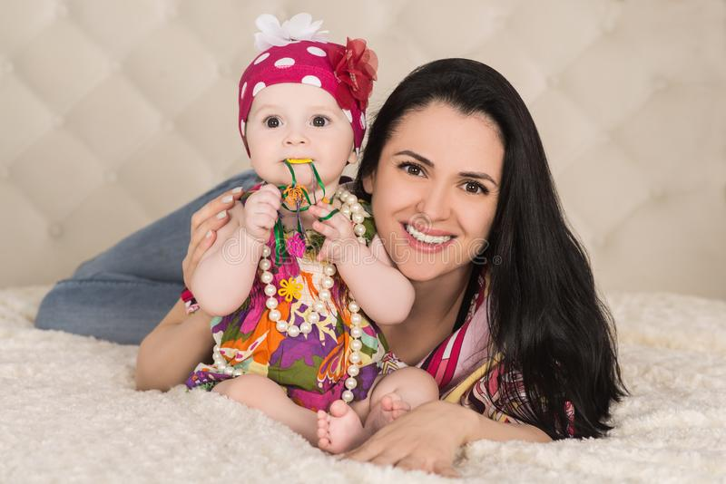 Retrato do bebê bonito com a mãe na cama, dentro fotografia de stock royalty free