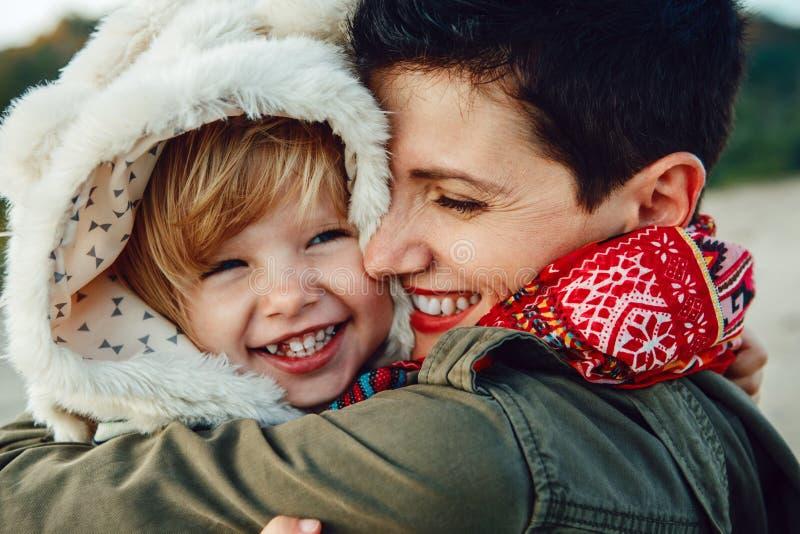 Retrato do bebê caucasiano branco da mãe e da filha que abraça o riso de sorriso jogando a corrida na praia do mar do oceano fotos de stock