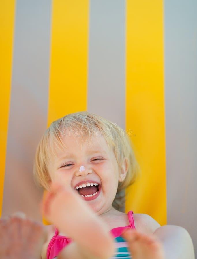 Retrato do bebê com nata do bloco do sol no nariz imagens de stock royalty free