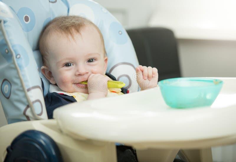 Retrato do bebê de sorriso adorável que come o papa de aveia próprio com sp foto de stock royalty free