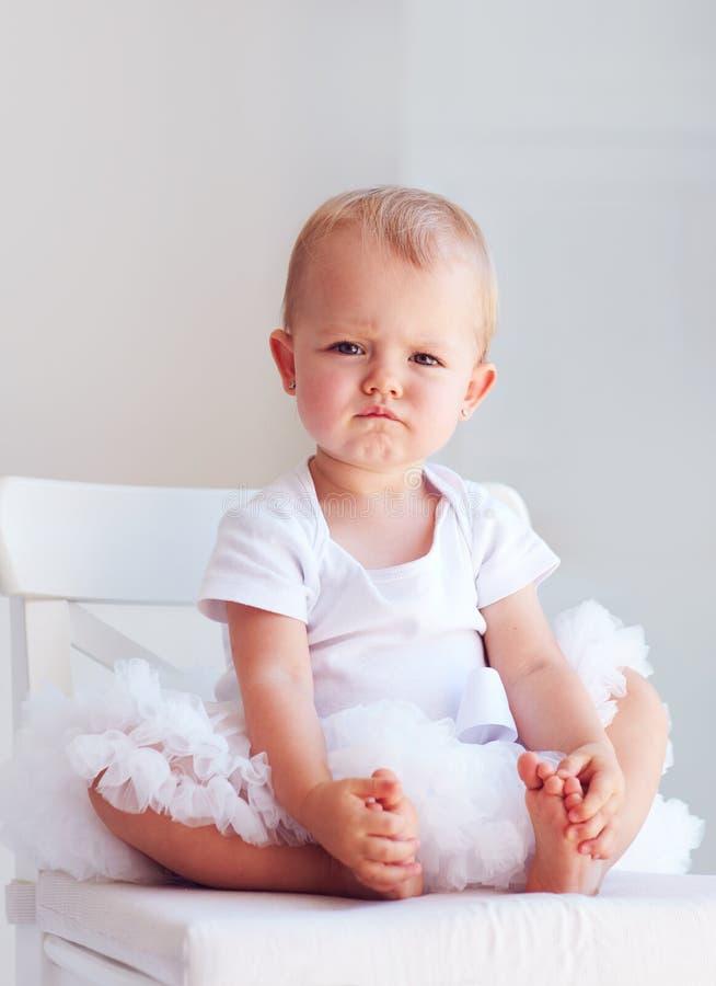Retrato do bebê de um ano com expressão séria da cara e a têmpera impetuosa que levantam na cadeira imagem de stock