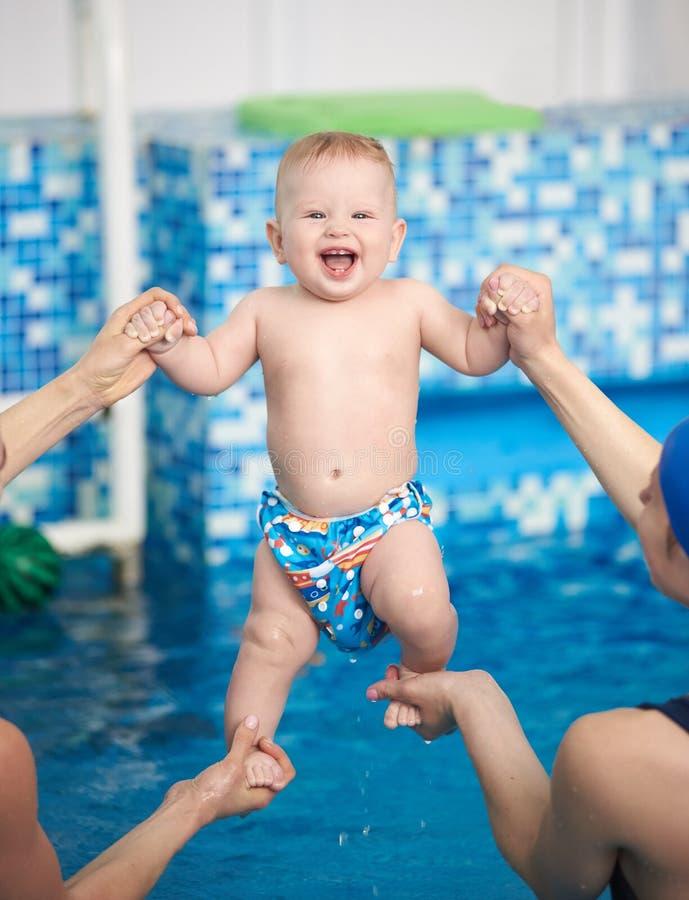 Retrato do bebê feliz adorável com sorriso toothy durante fazer o exercício na associação de remo sobre a água azul foto de stock royalty free