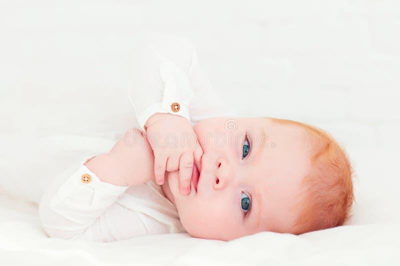 Retrato do bebê feliz do ruivo que encontra-se na barriga fotografia de stock
