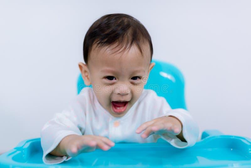 Retrato do bebê novo feliz na cadeira alta Criança que senta-se na tabela vazia imagem de stock