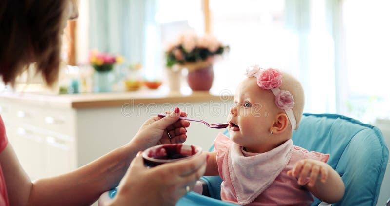 Retrato do bebê novo feliz na cadeira alta que está sendo alimentada fotos de stock royalty free