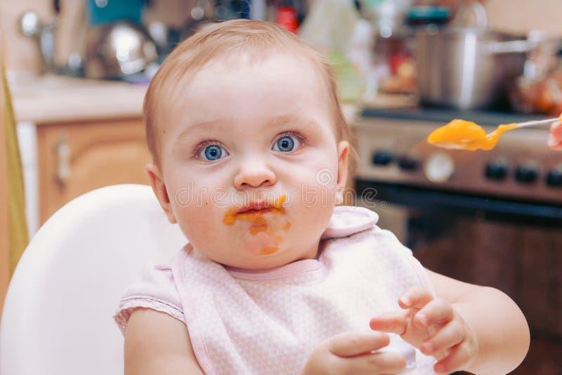 Retrato do bebê novo feliz na cadeira alta que está sendo alimentada foto de stock