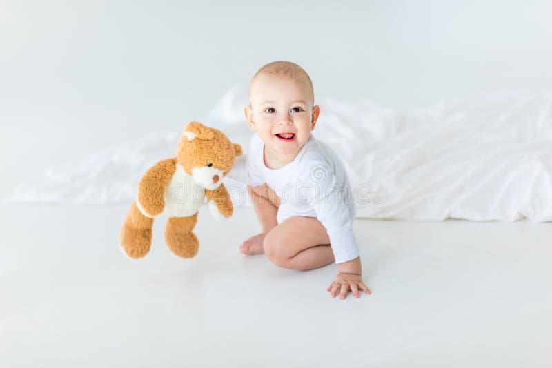 Retrato do bebê pequeno adorável com o urso de peluche que joga na cama imagem de stock