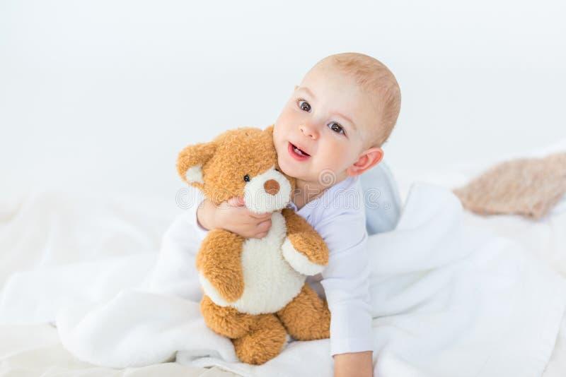 Retrato do bebê pequeno adorável com o urso de peluche que joga na cama foto de stock