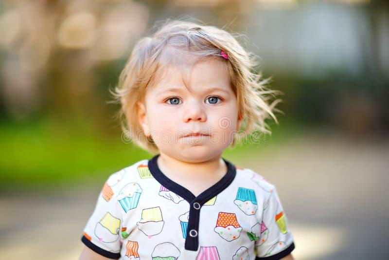 Retrato do bebê pequeno bonito no jardim da mola no dia ensolarado Criança de sorriso feliz bonita com rosa de florescência imagens de stock