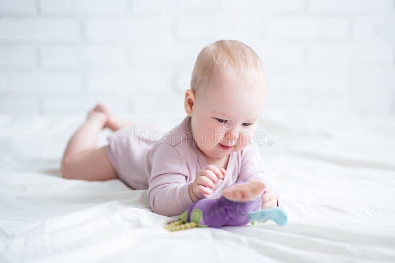 Retrato do bebê pequeno que encontra-se na cama com brinquedo fotografia de stock royalty free