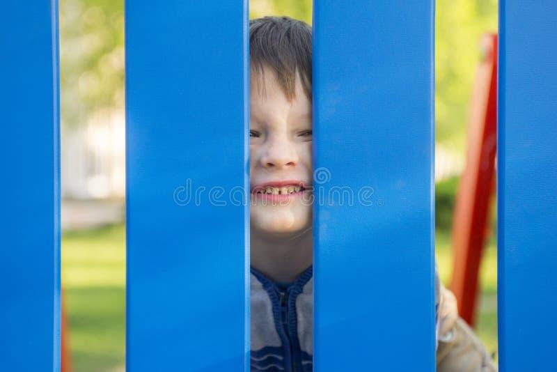 Retrato do bebê pequeno que olha para fora através da cerca fotos de stock