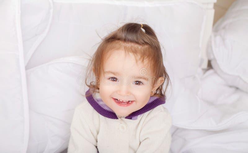 Retrato do bebê que encontra-se na cama sob featherbed foto de stock royalty free