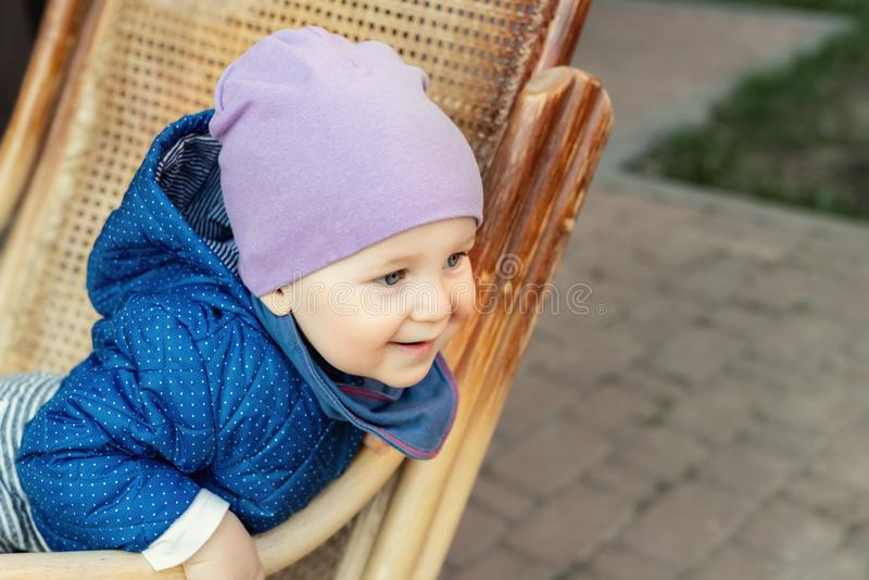 Retrato do beb? caucasiano ador?vel bonito que tem o divertimento que senta-se na cadeira de balan?o de madeira do rattan no quin fotos de stock
