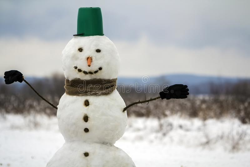 Retrato do boneco de neve feliz branco com o nariz alaranjado da cenoura, pedras pretas para os olhos e cubeta verde em sua cabeç foto de stock
