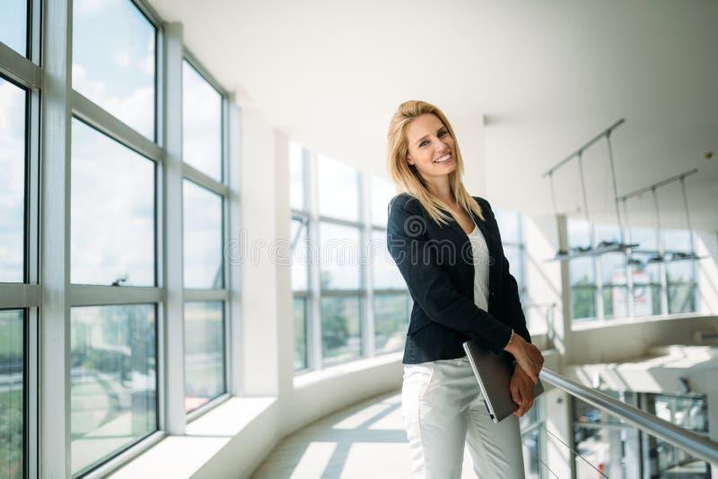 Retrato do busineswoman novo que está na entrada do escritório fotografia de stock royalty free
