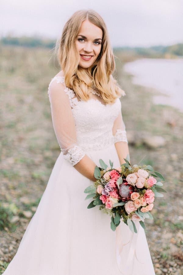 Retrato do busto da noiva de sorriso que guarda o ramalhete exótico do casamento no fundo da praia imagem de stock royalty free