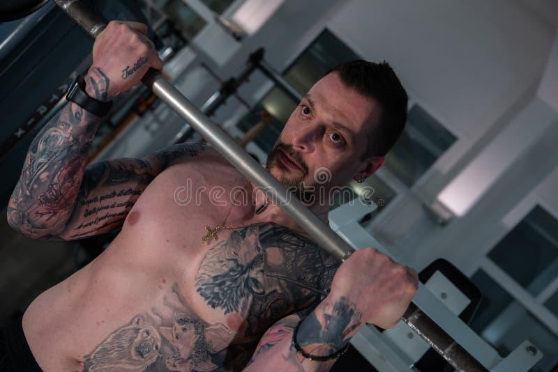 Retrato do busto de um menino com as tatuagens que fazem exercícios no gym imagens de stock royalty free