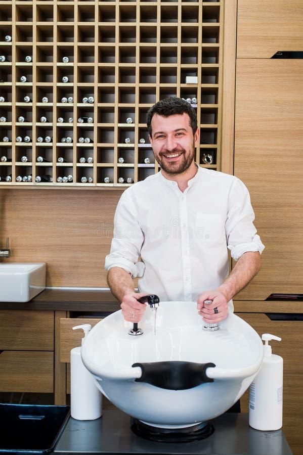 Retrato do cabeleireiro de sorriso considerável com a torneira de água perto do dissipador no barbeiro do salão de beleza foto de stock