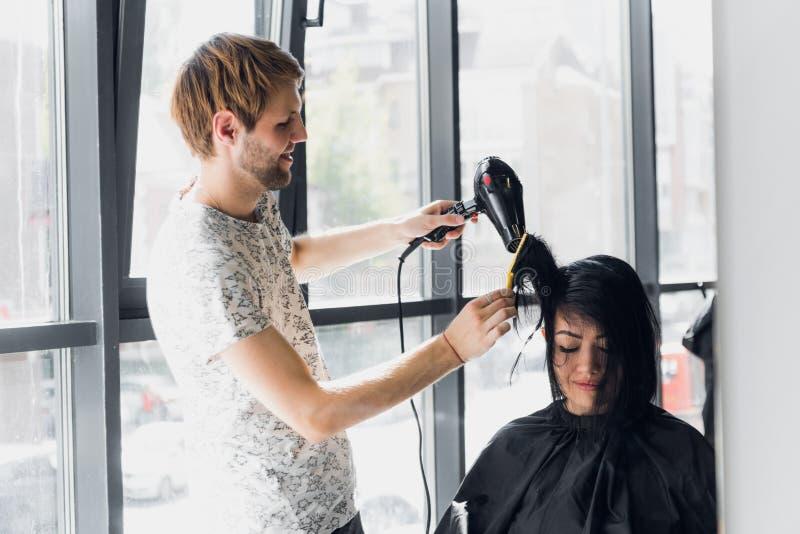 Retrato do cabeleireiro feliz que guarda o pente e o secador do sopro no salão de beleza fotografia de stock