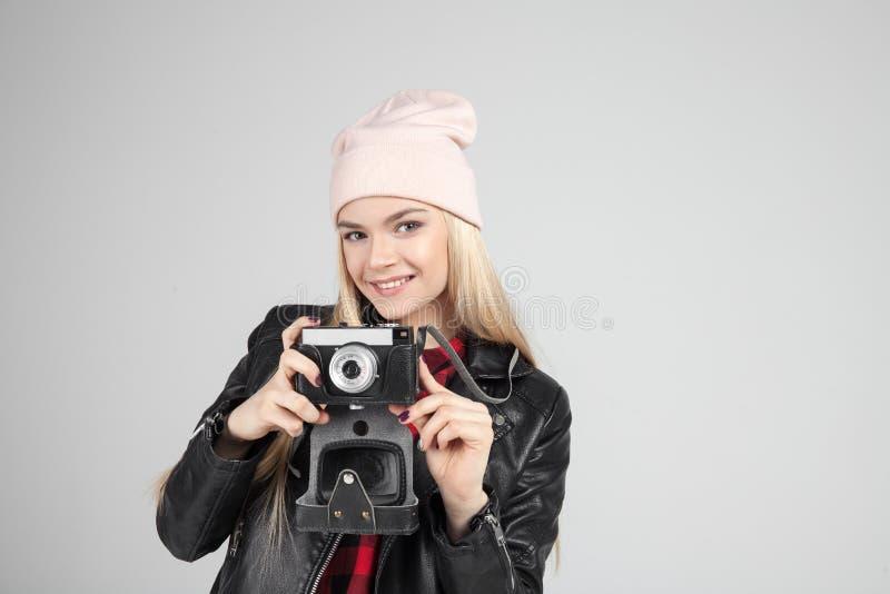 Retrato do cabelo consideravelmente louro que smileing o modelo adolescente novo da mulher do moderno com a câmera retro da foto  foto de stock
