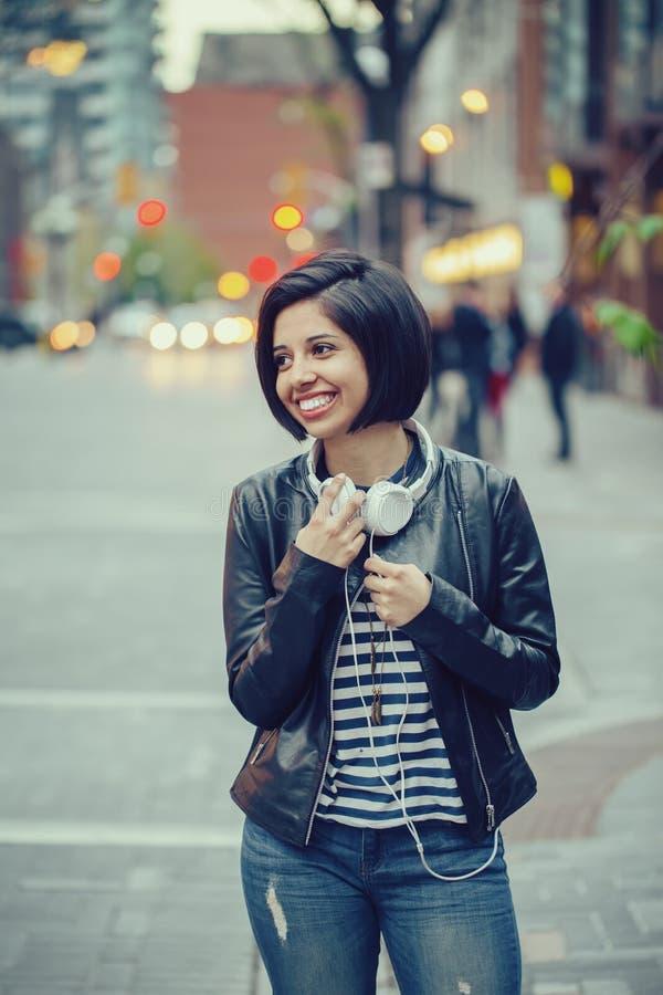 Retrato do cabelo preto curto da mulher latin latino-americano bonita da menina no casaco de cabedal com fones de ouvido imagens de stock