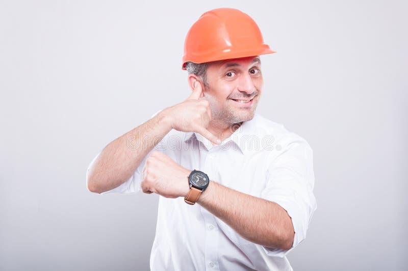 Retrato do capacete de segurança vestindo do arquiteto que mostra chamando o gesto fotos de stock