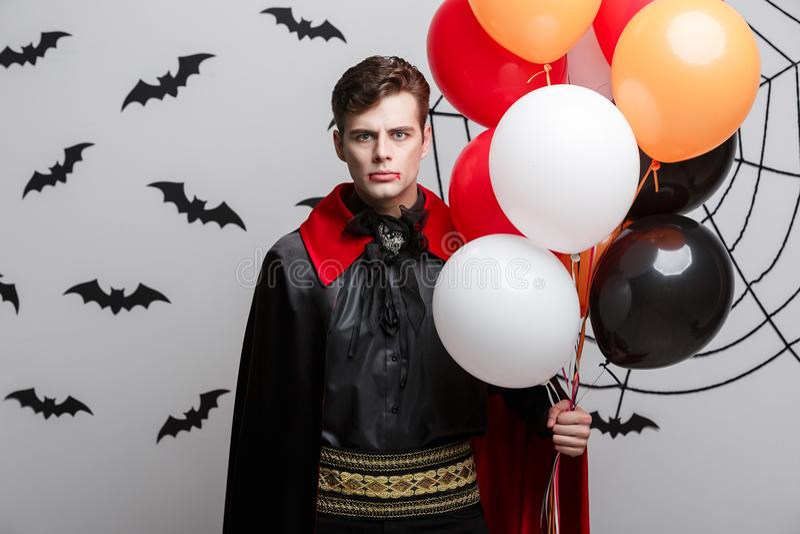 Retrato do caucasian considerável no traje do Dia das Bruxas do vampiro com balão colorido foto de stock royalty free