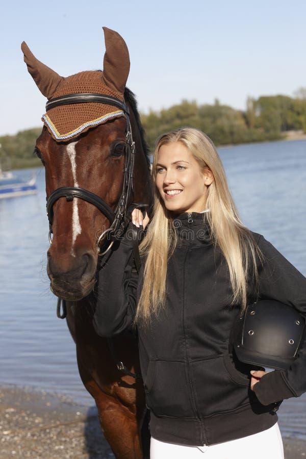 Retrato do cavaleiro e do cavalo fêmeas novos imagem de stock royalty free