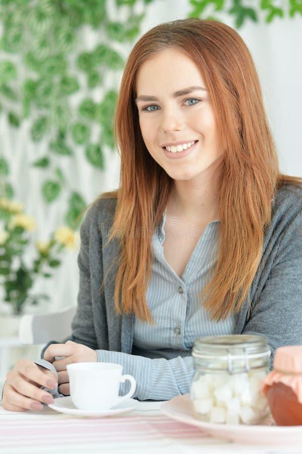 Retrato do chá bebendo da mulher nova bonita do ruivo foto de stock royalty free