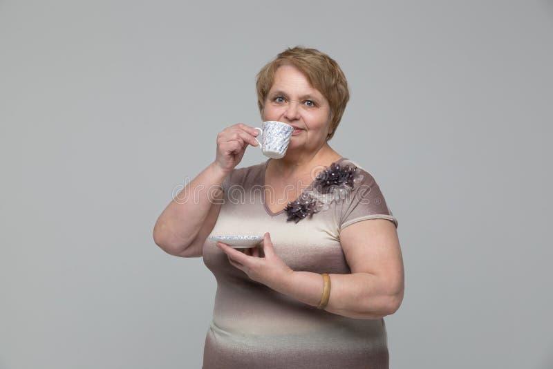 Retrato do chá bebendo de sorriso da mulher superior imagens de stock royalty free