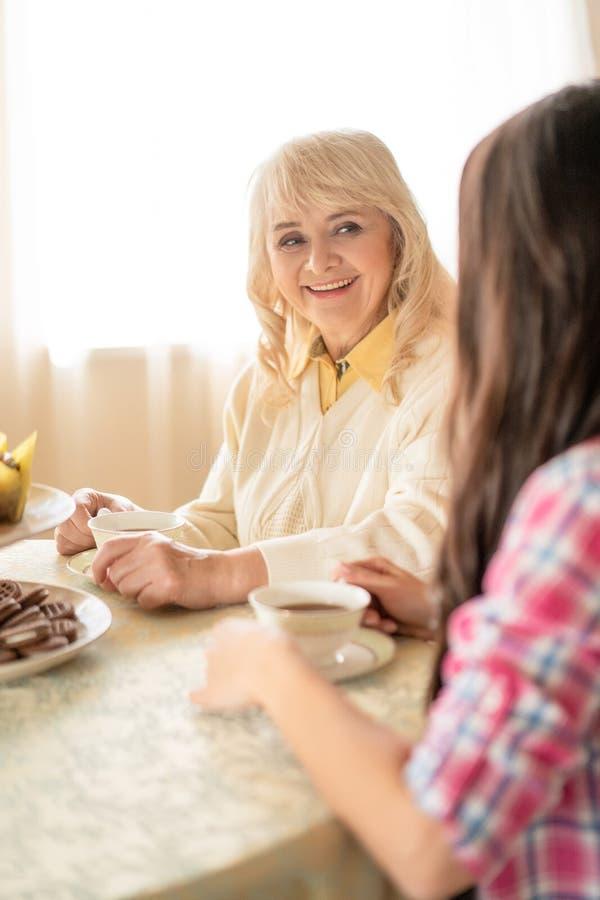 Retrato do chá bebendo e da fala da mulher superior bonita com filha levando foto de stock