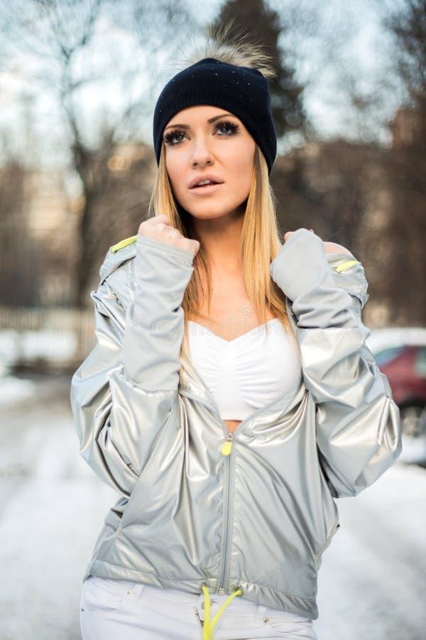 Retrato do chapéu da mulher loura atrativa e do revestimento vestindo da prata que olham a câmera ao levantar foto de stock