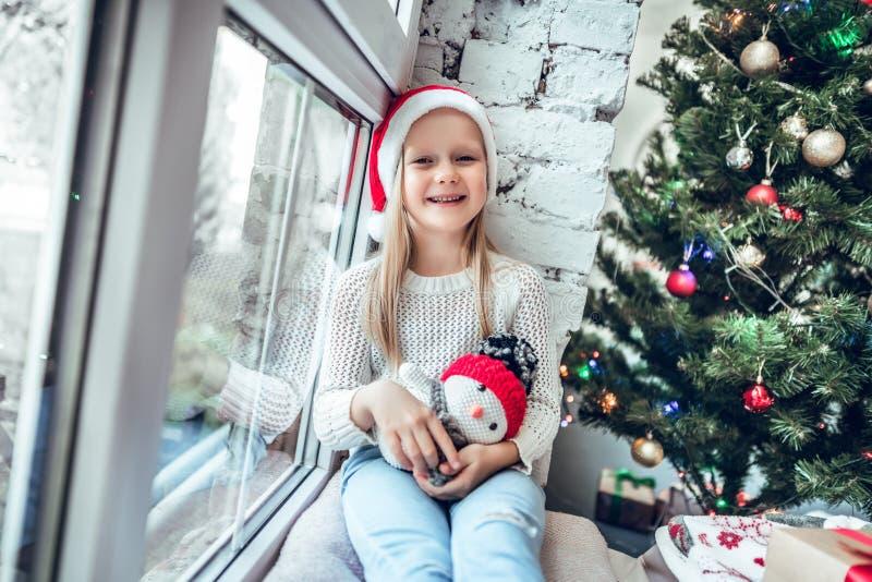 Retrato do chapéu vermelho vestindo do Natal da menina feliz bonito fotografia de stock