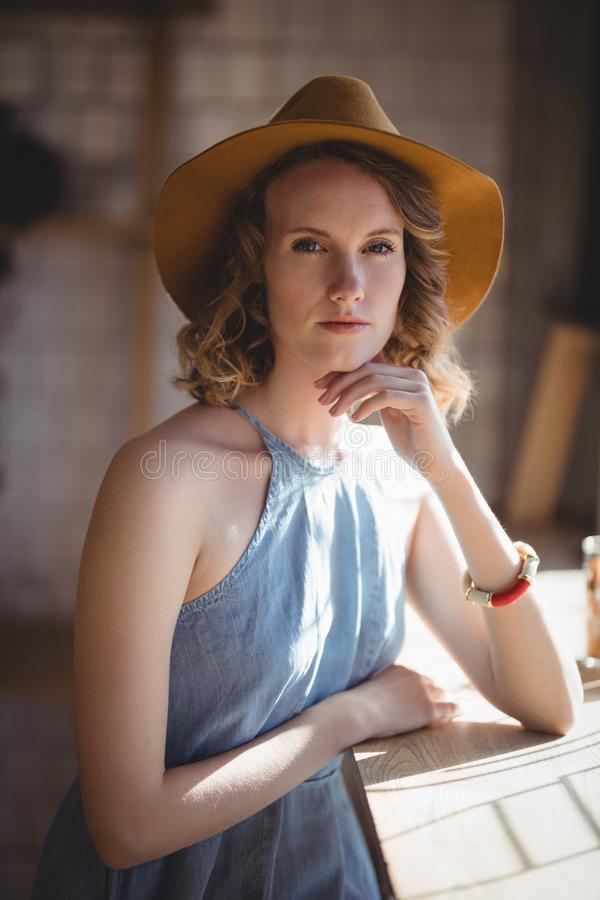 Retrato do chapéu vestindo da jovem mulher bonita que está na cafetaria imagem de stock royalty free
