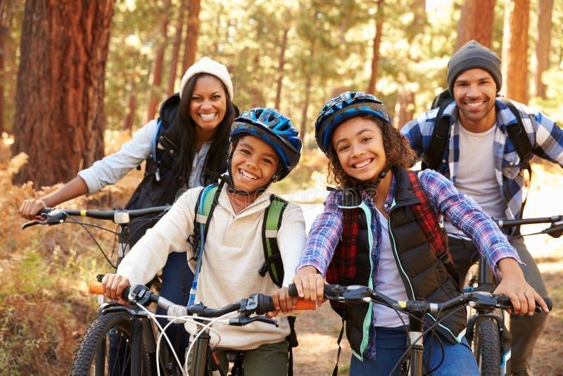 Retrato do ciclismo da família através da floresta da queda imagem de stock royalty free