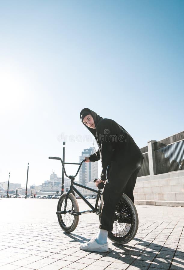 Retrato do ciclista que senta-se em bicicletas do bmx, olhando a câmera no fundo de uma cidade em um dia ensolarado imagens de stock royalty free