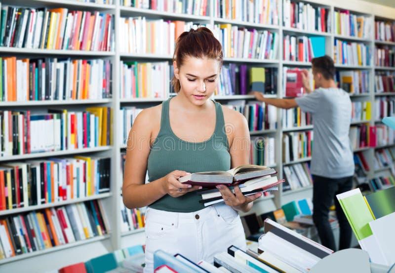 Retrato do cliente do adolescente que olha a posição aberta do livro foto de stock royalty free