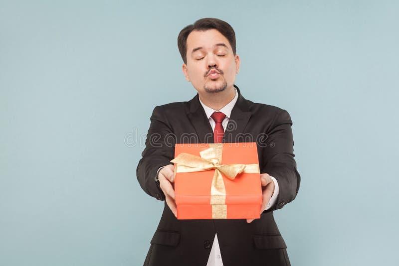 Retrato do close up da caixa de presente do presente do homem de negócio, beijo do ar fotografia de stock royalty free