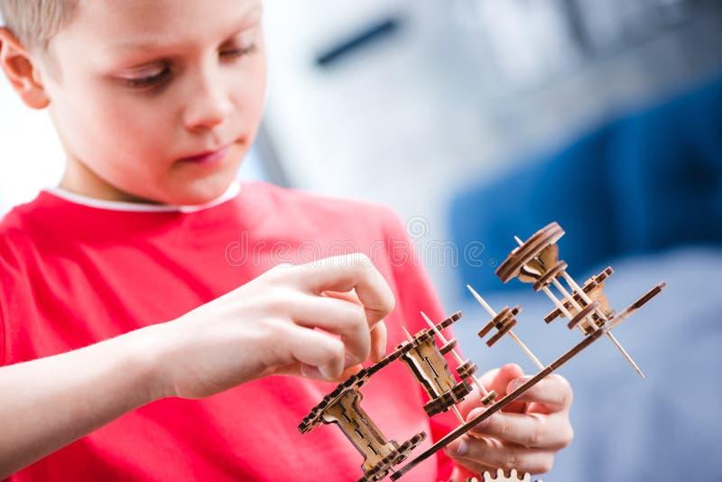 Retrato do close-up da criança concentrada que guarda a engrenagem de madeira fotos de stock royalty free