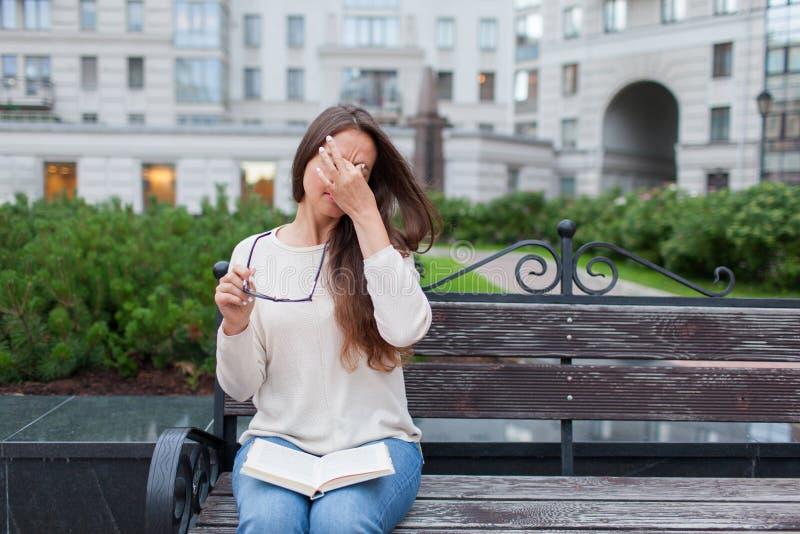 Retrato do close up da fêmea atrativa com monóculos à disposição A moça pobre tem edições com visão Fricciona seus nariz e olhos foto de stock royalty free